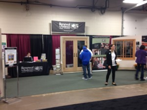Samantha waits to greet guests at the Home Show, while Richard goes over the features and benefits of RbA's patio doors with a customer.
